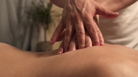 thérapie : Close-up of male masseur hands massaging back of woman in spa salon