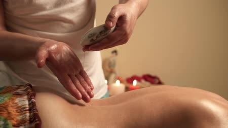 ayurveda : Close up of therapist pouring essential oil on female back in spa Stock Footage