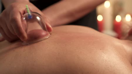 уход за телом : Young woman on procedure of vacuum cupping massage, close up