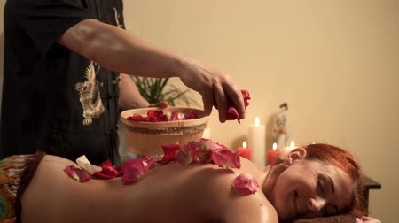 masszőr : Male massage therapist pours rose petals on back of female client after massage in spa salon