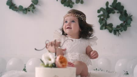 first person : Baby girl in white dress sitting on floor near birthday cake on his first birthday
