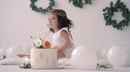 çelenk : Happy baby in white dress is sitting near festive cake on her first birthday party surrounded by balloons