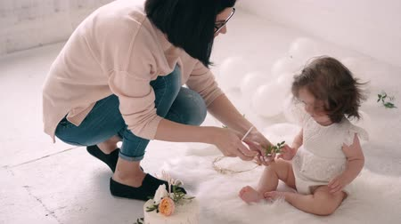 幼稚な : Woman photographer is combing baby girl before taking pictures of her in photo studio. 動画素材