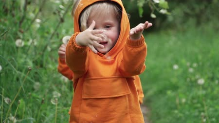 piada : Little boy in orange suit holding dandelion and looking at camera, slow motion Stock Footage