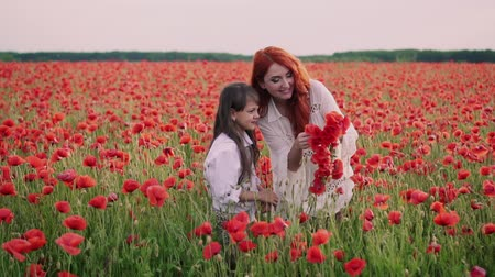 koszorú : Mom and little daughter make wreaths of poppy flowers in flowered field