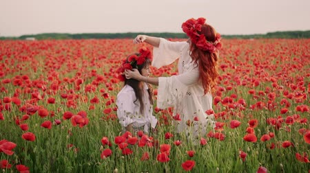 çelenk : Young mother puts wreath of poppy flowers on her daughters head, slow motion