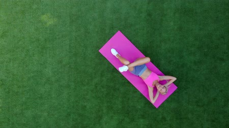 sakk : Top view young sporty woman performs twisting while lying on grass Stock mozgókép