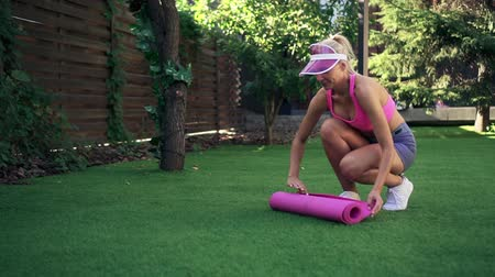pilates : Young woman rolls apart pink fitness mat on green grass, slow motion Stock Footage