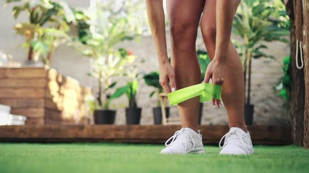 resistant : Woman puts on resistant band before exercise, close-up of legs Stock Footage