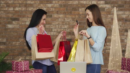 платить : Two girlfriends show each other their purchases, black Friday concept. Стоковые видеозаписи