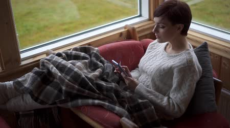 algılayıcı : Woman in comfortable chair uses smartphone on rainy day Stok Video