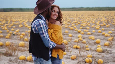 благодарение : Couple stands in pumpkin field and hugs, close up Стоковые видеозаписи