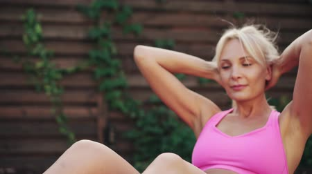 buikspieren : Young athletic woman trains abdominal muscles lying on green grass Stockvideo