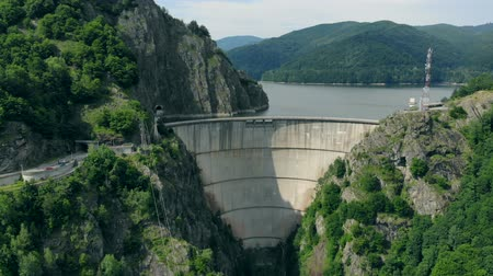 reservoir : Aerial view of a hydroelectric dam in the mountains covered with forest, the drone flies back Stock Footage
