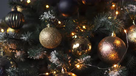 christmas ball gold : Close-up decorative balls and garlands on a Christmas tree on a dark background Stock Footage