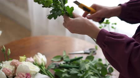 обрезки : Woman florist cleans the stems of plants from leaves in the manufacture of a bouquet, close-up of hands