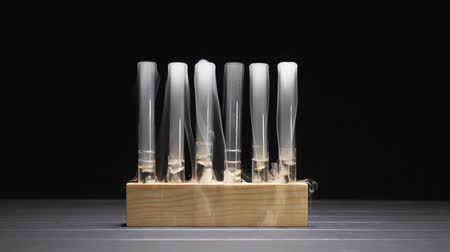 artigos de vidro : Smoky glass test tubes with dry ice on a black background. Close up. Vídeos