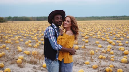 uğursuz : A young interracial couple stands embracing in a pumpkin field. Stok Video