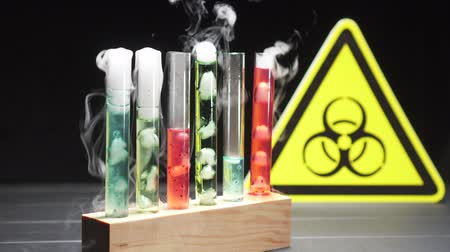 bung : Glass test tubes with boiling liquid of different colors against the background of the biohazard sign. Close-up.