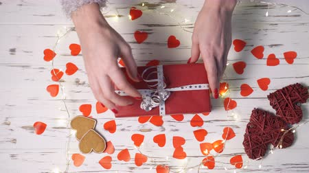 darovat : Female hands put a gift box on the desk, top view down. Valentines day concept.