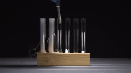 pipeta : Adding water to glass tubes with dry ice and subsequent smoke emission, close-up. Archivo de Video