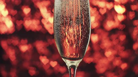 şarap kadehi : Champagne is poured into a glass on a red background with many hearts. Valentines day concept.