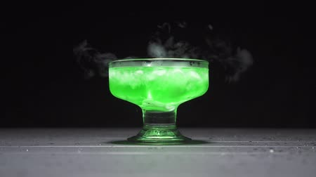 czary : Green liquid boils emitting a smoke in a glass bowl on a black background, close up.