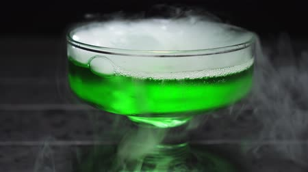 dioxid : Green liquid boils in a glass bowl, the chemical reaction of water to the addition of dry ice, close up.