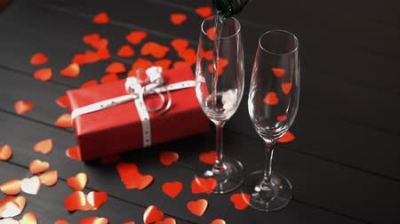 kırmızı şarap : Champagne is filled into a glass on a black table near a gift box, slow motion. Valentines day concept. Stok Video