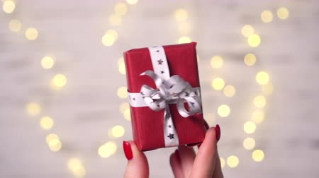kerstpakket : Close-up of a womans fingers holding a small gift box on a white background with blurry lights.