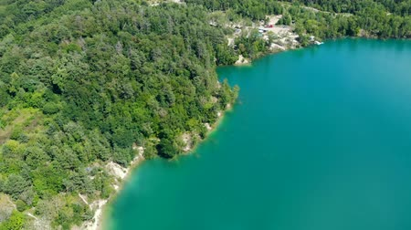emerald green : Aerial view of a blue lake surrounded by forest. Summer day. Stock Footage