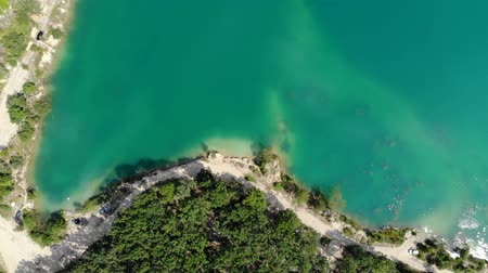 emerald green : Aerial view of a blue lake surrounded by forest. Top down view. Stock Footage