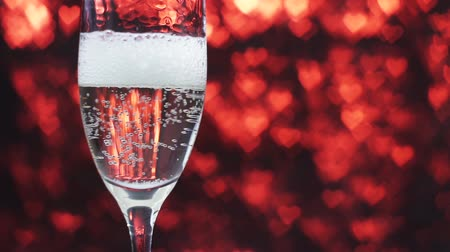 kırmızı şarap : Champagne is poured into a glass on a red background with many hearts, slow motion. Valentines day concept.