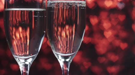 kırmızı şarap : Champagne is poured into a glass on a red background with many hearts. Valentines day concept.