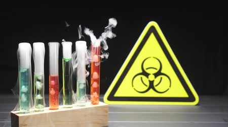 sindrome : Test tubes with boiling multi-colored liquid on the background of the biohazard sign. Coronavirus epidemic concept.