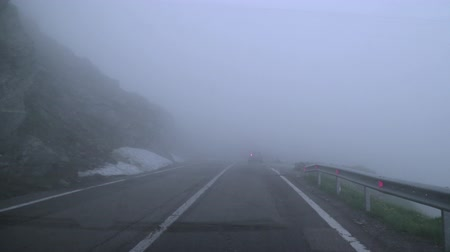 serpentine : POV driving on a mountain road covered in dense fog. Stock Footage