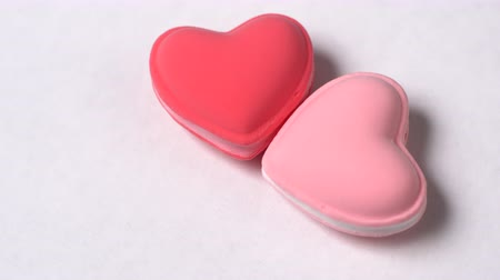 миндальное печенье : Two heart-shaped macaroons rotate on a white background. Valentines day concept.