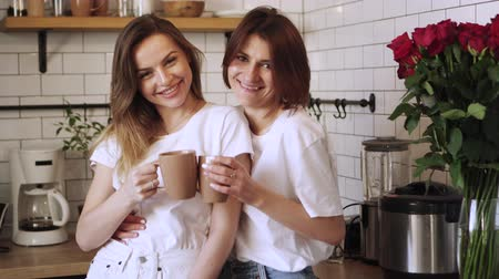 lesbian couple : Two young laughing lesbians drink coffee hugging at home in the kitchen. LGBT Community Concept. Stock Footage