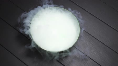 toverdrank : A gloved hand throws dry ice into a bowl of water, a chemical reaction occurs with smoke, top view.