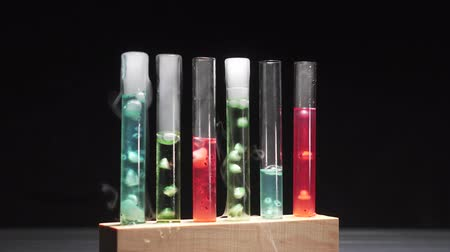 artigos de vidro : Glass test tubes with boiling multi-colored liquid on a black background, close-up. Scientific research concept.