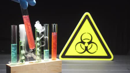 influenza background : Doctor hand takes a test tube with red liquid, against the background of the biohazard sign, close-up. Coronavirus epidemic concept. Stock Footage