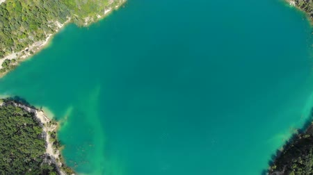 emerald green : Aerial view of a blue lake surrounded by forest. The drone rises.