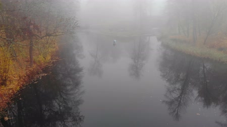 The drone slowly flies over the water surface of the lake in a foggy autumn park.