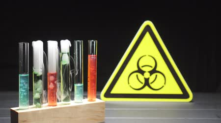 ingrandimento : Doctor hand takes a test tube with red liquid, against the background of the biohazard sign, close-up. Coronavirus epidemic concept. Filmati Stock