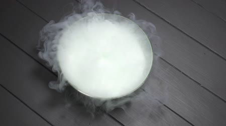 A gloved hand throws dry ice into a bowl of water, a chemical reaction occurs with smoke, slow motion.