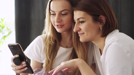 Two young women choose things in the online store using a smartphone. Close up.