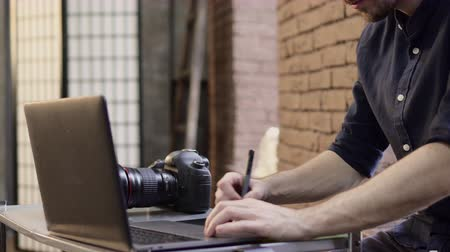 using stylus : Cropped young male photographer uses a graphics tablet to retouch images. Slider shot. Stock Footage