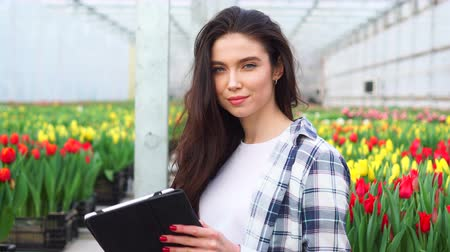 Young beautiful florist woman with tablet in hands standing in a greenhouse and smiling, close-up.
