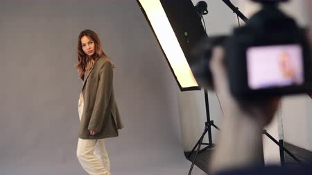 oturum : Young woman model dressed in 90s style clothes poses for a professional photographer in the studio. Stok Video