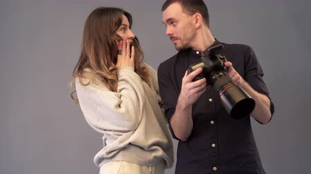 oturum : Male photographer and female model are watching captured images on the camera screen. They are pleased with the result of the photo shoot. Close up.